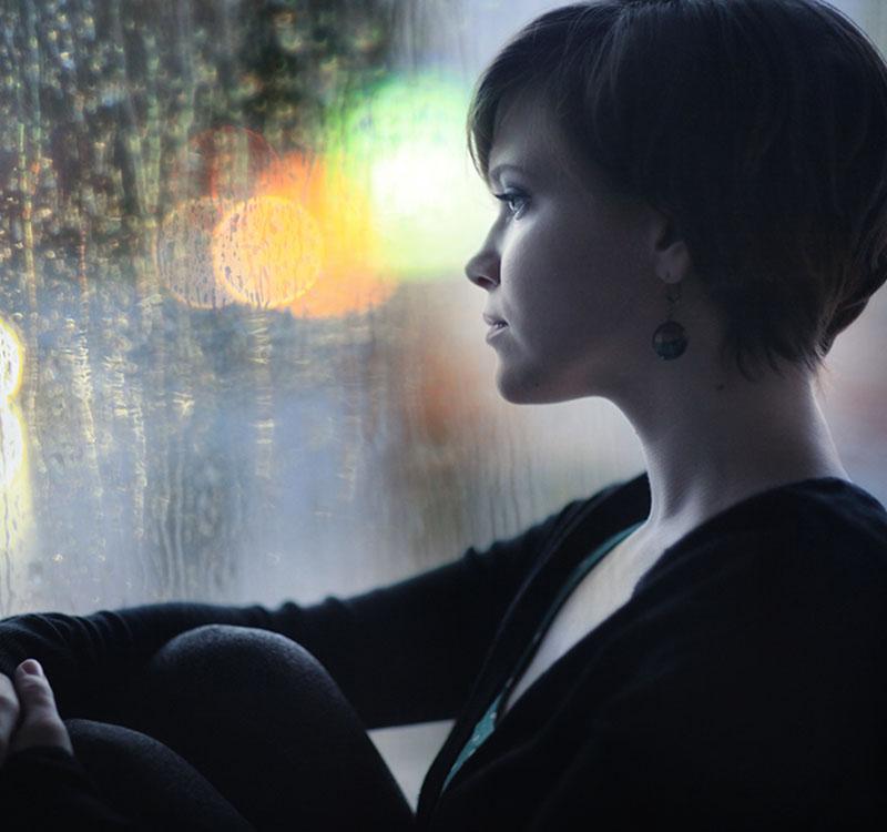 sad girl on the windowsill looking out the window